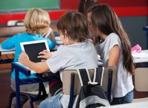 Rear view of little schoolchildren using digital tablet at desk in classroom